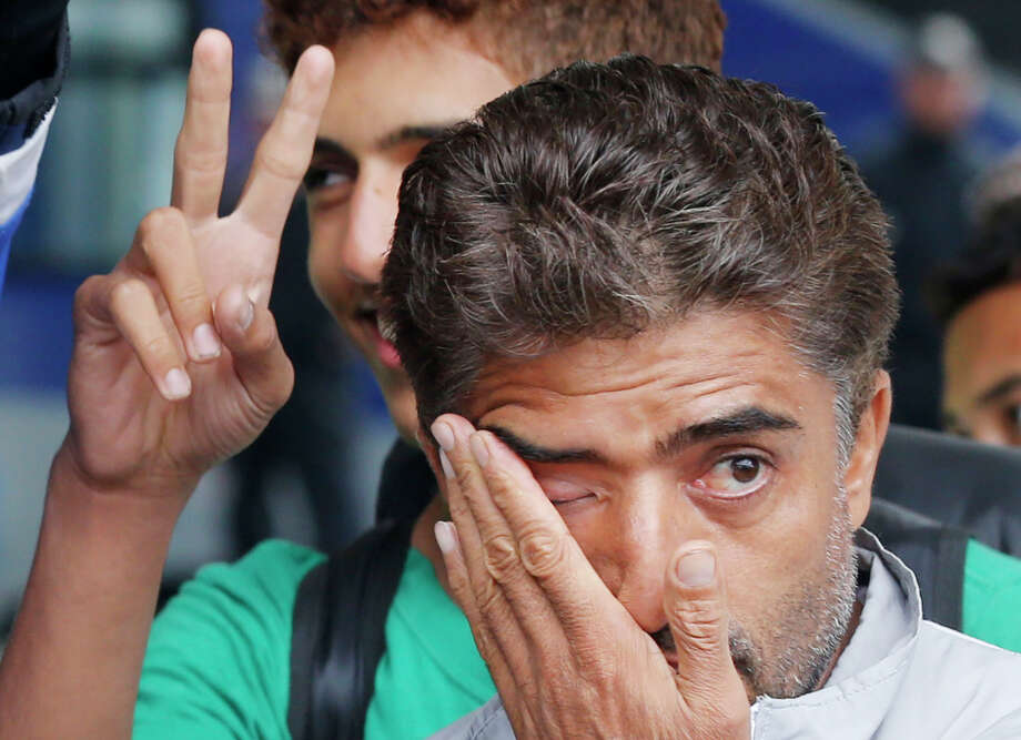 Refugees flash victory signs and wipe away tears as they arrive at the main train station in Munich, Germany, Saturday, Sept. 5, 2015. Hundreds of refugees arrived in various trains to get first registration as asylum seekers in Germany. (AP Photo/Michael Probst) Photo: Michael Probst, STF / AP
