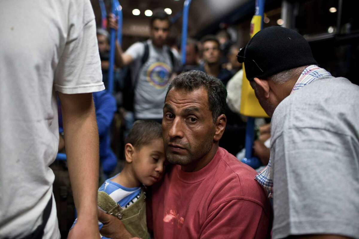 A man and a child ride aboard a bus provided by Hungarian authorities for migrants and refugees at Keleti train station in Budapest, Hungary, Saturday, Sept. 5, 2015. Hundreds of migrants boarded buses provided by Hungary's government as Austria in the early-morning hours said it and Germany would let them in. Austrian Chancellor Werner Faymann announced the decision early Saturday after speaking with Angela Merkel, his German counterpart - not long after Hungary's surprise nighttime move to provide buses for the weary travelers from Syria, Iraq and Afghanistan. (AP Photo/Marko Drobnjakovic)