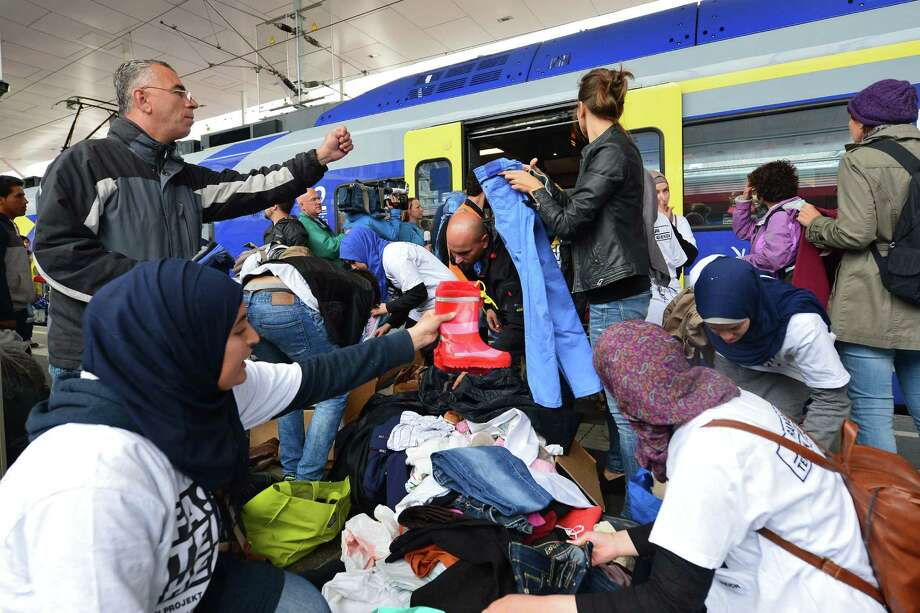 Refugees receive new clothes as they arrive at the Hauptbahnhof station in Salzburg, Austria, Saturday, Sept. 5, 2015, on their way from Hungary via Vienna to Germany. Photo: Kerstin Joensson, AP / AP