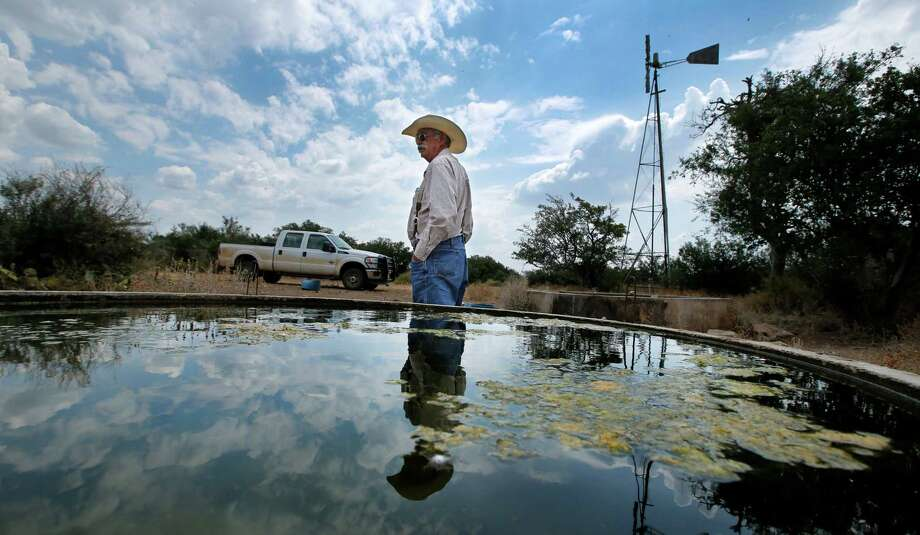 Rancher Ron Crocker, who owns CA Cattle Company outside Mason, checks on his windmill-driven freshwater stock pools. A proposal by an Italian energy developer to build a wind farm in the heart of Hill Country has stirred up the ire of locals. Photo: Tom Fox, MBR / The Dallas Morning News