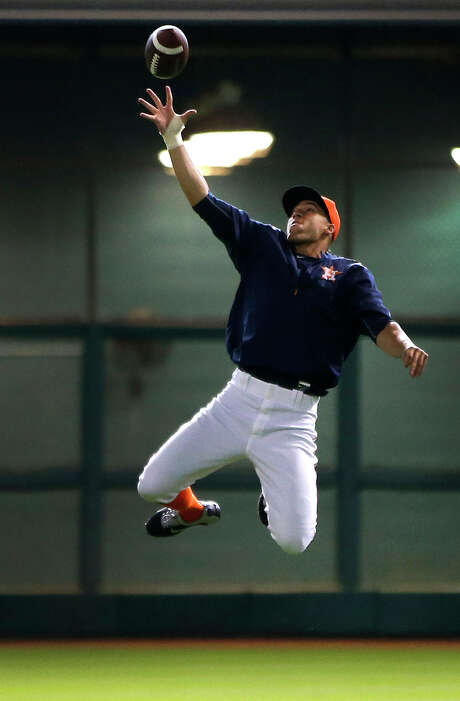 With college football getting underway this weekend, Astros outfielder George Springer, who attended the University of Connecticut, shows off his pass-catching skills before the start of Saturday's game at Minute Maid Park. Photo: Karen Warren, Staff / © 2015 Houston Chronicle