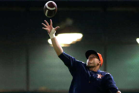 With college football getting underway this weekend, Astros outfielder George Springer, who attended the University of Connecticut, shows off his pass-catching skills before the start of Saturday's game at Minute Maid Park.