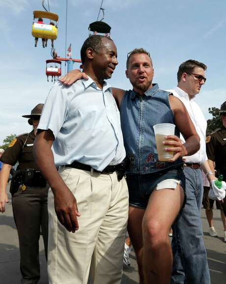 Republican presidential candidate Ben Carson, posing with an Iowa State Fair attendee, is the one of the outsider candidates who are resonatng with voters in both parties. Photo: Charlie Riedel, STF / AP