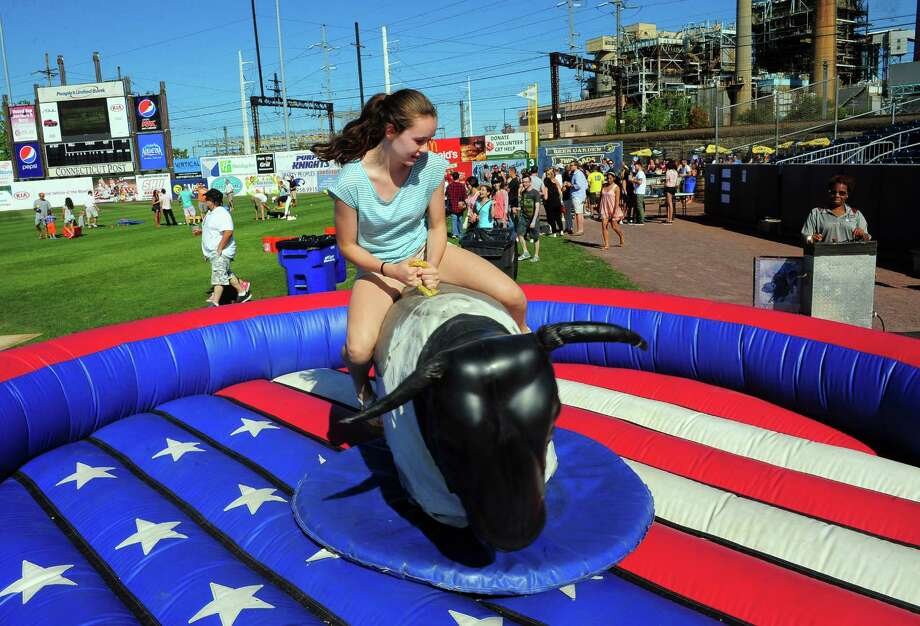 Grace Boles, 14, of Shelton, takes a ride on a mechanical bull during the 1st Annual 'Fish Fest hosted by the Bridgeport Bluefish baseball team at the Ballpark at Harbor Yard in Bridgeport, Conn., on Saturday Sept. 5, 2015. âÄúOur fans often say that they would love for us to host some sort of annual event at the Ballpark,âÄù says Bluefish General Manager Jamie Toole. âÄúAnd everybody knows, you can never have too many live music events during the summer months. So we decided to combine these two things into one event and we came up with the concept for âÄòFish Fest.âÄù This yearâÄôs festival will have a country music theme, and will feature performances from a total of seven live acts, including Mark Wills, Girls Guns & Glory, Tat Holler, Jump The Gunn, Wastin' Bullets, Jay Taylor, and Bill Haug. âÄòFish Fest will also feature a mechanical bull, a dunk tank, rides and inflatables, and the Two Roads Beer Garden will be open. Photo: Christian Abraham, Hearst Connecticut Media / Connecticut Post