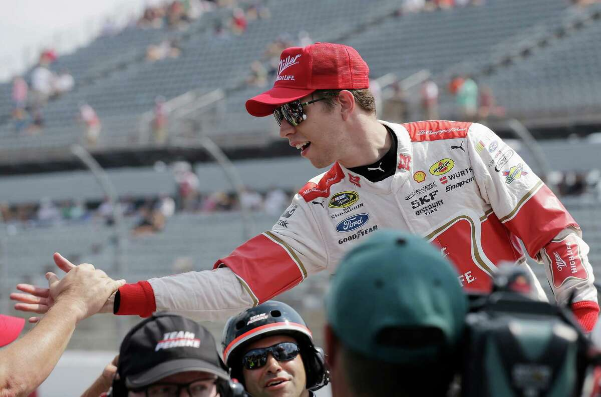 Brad Keselowski is congratulated by crew members after winning the pole for Sundays NASCAR Sprint Cup auto race at Darlington Raceway in Darlington, S.C., Saturday, Sept. 5, 2015. (AP Photo/Terry Renna) ORG XMIT: SCTR104