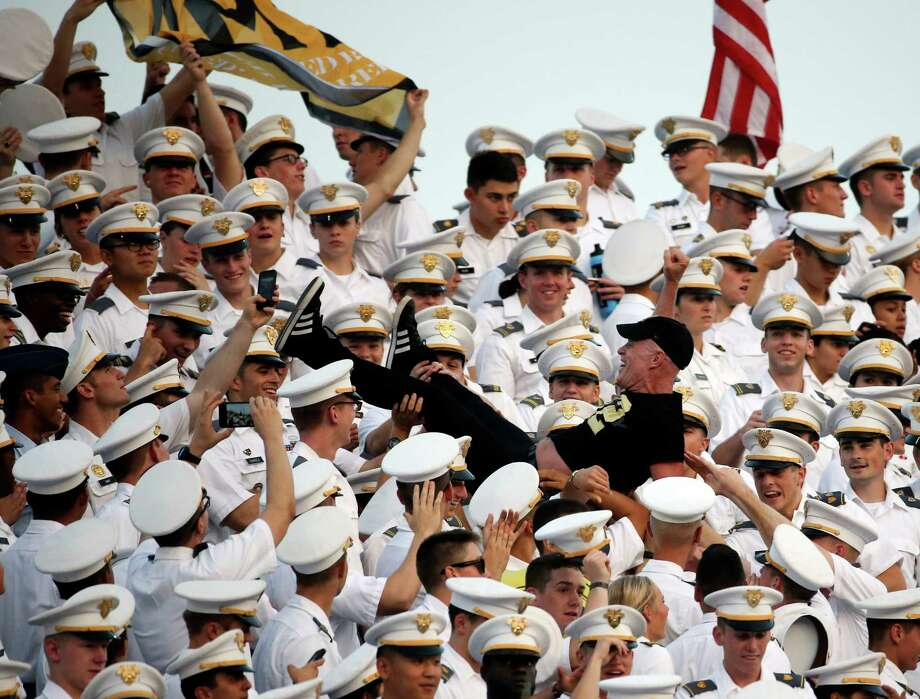 """In this Friday, Sept. 4, 2015 photo, a man is passed through the cadet cheering section during the first half of an NCAA college football game between Army and Fordham in West Point, N.Y. Two dozen cadets suffered concussions on Aug. 20, 2015, during the annual pillow fight by first year students known as """"plebes."""" Some cadets swung pillow cases filled with hard objects according to a story in the New York Times, published Saturday, Sept. 5. (AP Photo/Mike Groll) Photo: Mike Groll, STF / AP"""