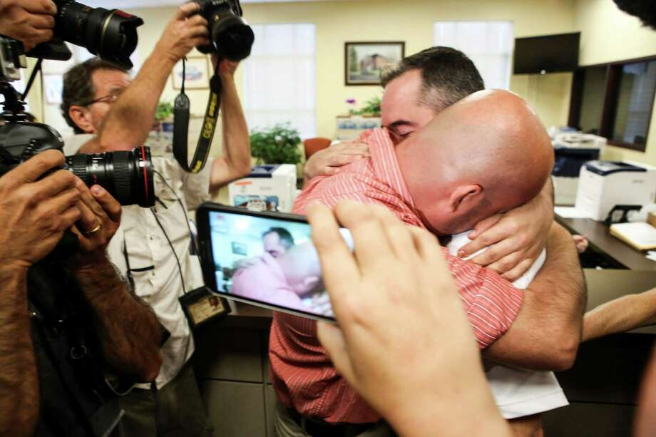 James Yates (right) hugs William Smith Jr. after receiving their marriage license in Rowan County. Photo: Alton Strupp /Associated Press / The Courier-Journal