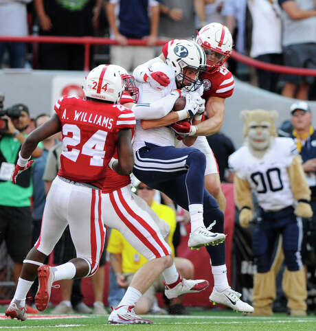 BYU wide receiver Mitch Mathews, center, catches the game-winning touchdown between Nebraska defensive back Aaron Williams (24) and safety Nate Gerry (25)  as time runs out in the fourth quarter of an NCAA college football game, to give BYU a 33-28 victory over Nebraska at Memorial Stadium on Saturday, Sept. 5, 2015 in Lincoln, Neb. (Eric Gregory/The Journal-Star via AP) LOCAL TELEVISION OUT; KOLN-TV OUT; KGIN-TV OUT; KLKN-TV OUT; MANDATORY CREDIT Photo: Eric Gregory, MBI / Lincoln Journal Star