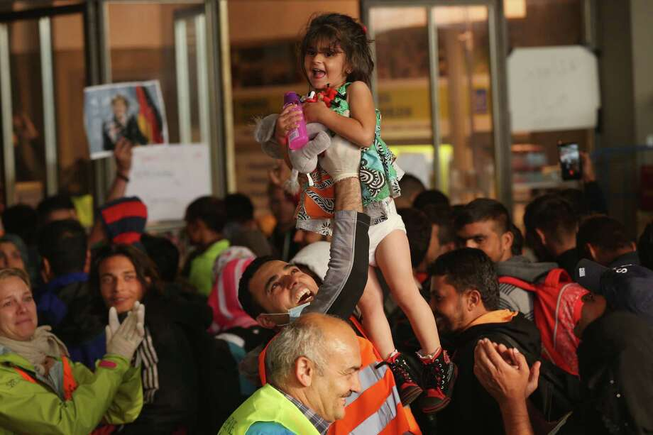 A volunteer holds up a child who was among hundreds of migrants who had arrived on a train from Hungary at a Munich railway station. Photo: Sean Gallup /Getty Images / 2015 Getty Images