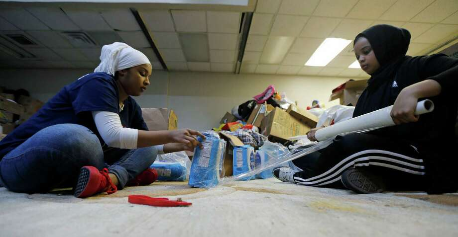 Latifah Muridi left, and Aisha Hagi wrap sugar in plastic before boxing it at the Warehouse of Helping Hand For Relief & Development. The group hopes to help feed 650 Syrian refugee families in Jordan. Photo: James Nielsen, Staff / © 2015  Houston Chronicle
