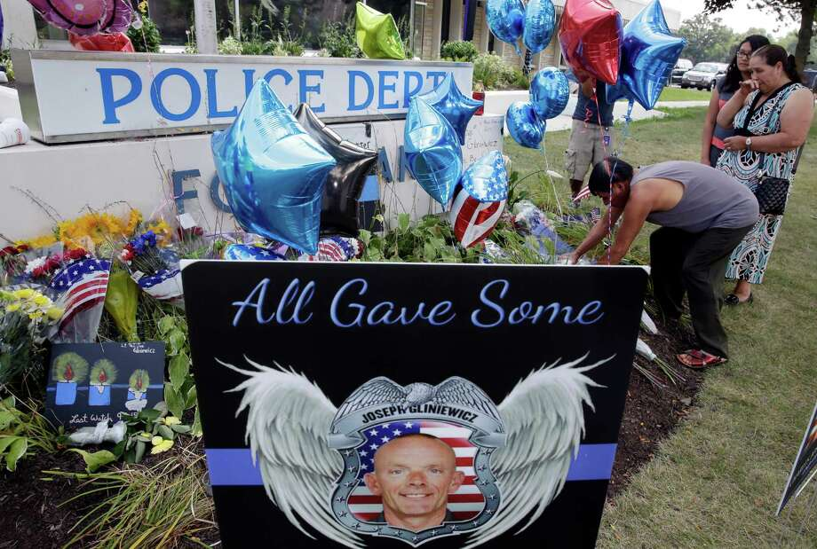 People pay respects to Lt. Joe Gliniewicz at a makeshift memorial outside the Fox Lake Police department on Wednesday, Sept. 2, 2015, in Fox Lake, Ill. Fox Lake Police Lt. Charles Joseph Gliniewicz was shot and killed Tuesday while pursuing a group of suspicious men. Police are searching for a second day to locate three suspects in the killing. (AP Photo/Nam Y. Huh) Photo: Nam Y. Huh, STF / Associated Press / AP