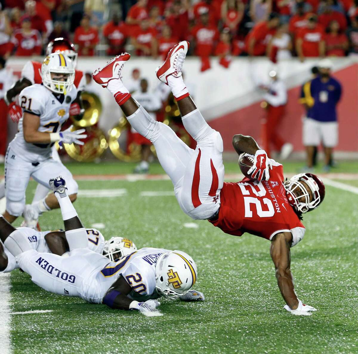 UH's Ryan Jackson sails over Tennessee Tech players for a short gain Saturday Sept. 5, 2015