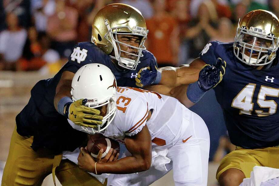 SOUTH BEND, IN - SEPTEMBER 05: Jerry Tillery #99 of the Notre Dame Fighting Irish tackles Jerrod Heard #13 of the Texas Longhorns for a loss of yards during the second quarter at Notre Dame Stadium on September 5, 2015 in South Bend, Indiana. Photo: Jon Durr, Getty Images / 2015 Getty Images