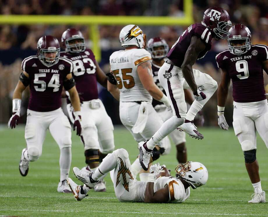 Texas A&M Aggies defensive back Donovan Wilson (6) jumps over Arizona State Sun Devils running back De'Chavon Hayes (1) during the first half of a college football game during the Advocare Texas Kickoff game at NRG Stadium on Saturday, Sept. 5, 2015.  ( Karen Warren / Houston Chronicle ) Photo: Karen Warren, Staff / © 2015 Houston Chronicle