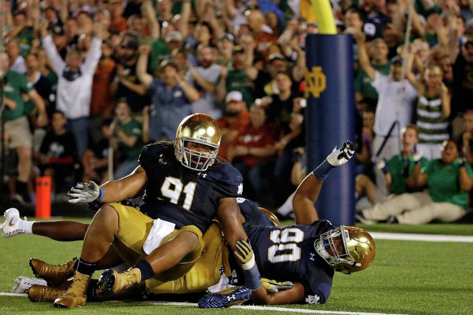 SOUTH BEND, IN - SEPTEMBER 05: Sheldon Day #91 of the Notre Dame Fighting Irish and Isaac Rochell #90 celebrate after making a tackle for a loss of yards against the Texas Longhorns during the second quarter at Notre Dame Stadium on September 5, 2015 in South Bend, Indiana.  (Photo by Jon Durr/Getty Images) Photo: Jon Durr, Stringer / 2015 Getty Images