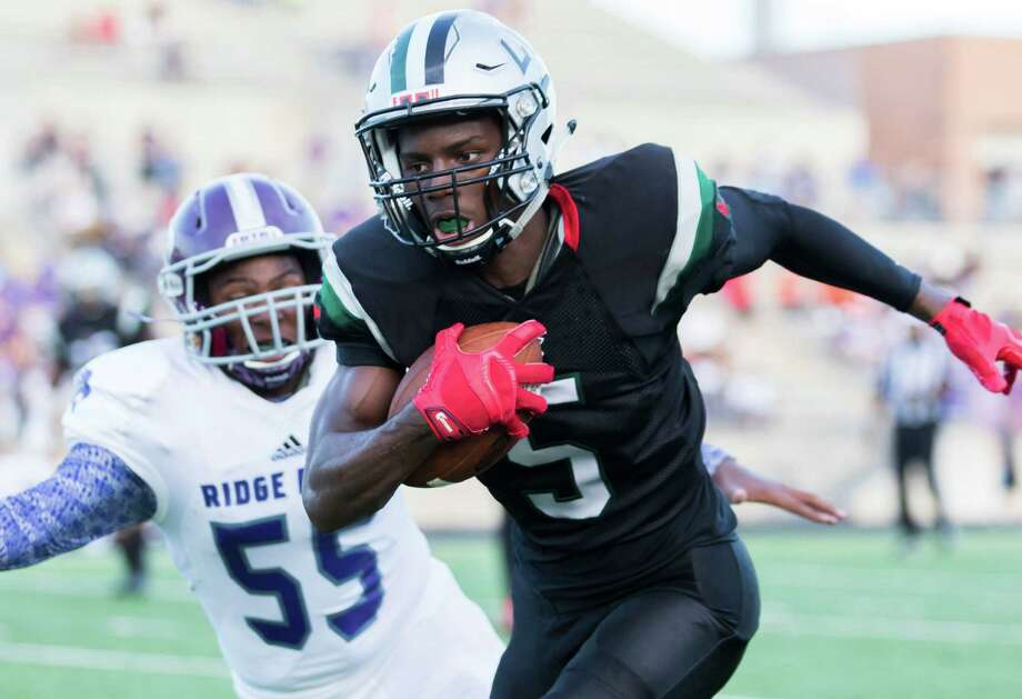 Hightower's Terrance Cooper (5) looks for running room after catching a pass from quarterback Neiko Hollins in the second quarter of the Hurricanes' win over Ridge Point on Saturday at Hall Stadium. Photo: Joe Buvid, Freelance / © 2015 Joe Buvid