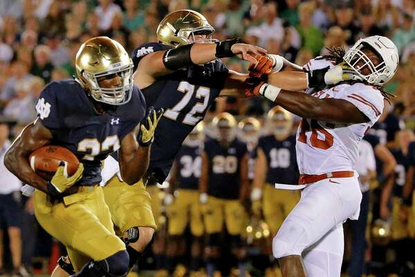 Nick Martin of the Notre Dame Fighting Irish blocks Jermaine Roberts of the Texas Longhorns as Josh Adams rushes for a touchdown against the Texas Longhorns during the third quarter at Notre Dame Stadium on Sept. 5, 2015 in South Bend, Ind.