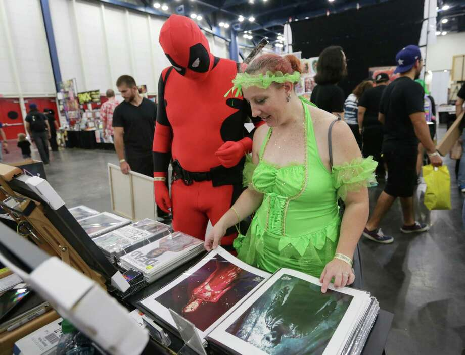 Kathleen Wilkinson, right, and Jerad Mattingly, left, look at prints by Tom Carlton at the Amazing! Houston Comic Con at the George R. Brown convention center, Saturday, Sept. 5, 2015, in Houston. The pair has been to a number of the larger conventions on the west coast, but this weekend was their first convention in Texas. Photo: Jon Shapley, Houston Chronicle / © 2015 Houston Chronicle