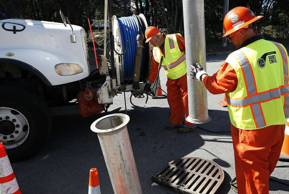 Efren Campos, right, and John Mattias, of the Public Utilities Commission's sewer operations department, clean catch basins in preparation for El Nino rains in San Francisco, Calif., on Friday, September 4, 2015.