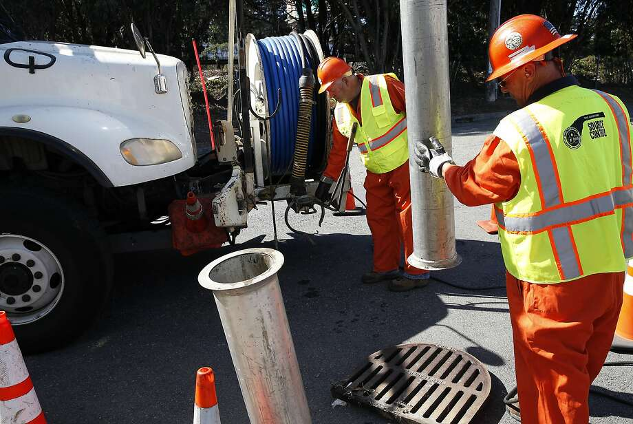 Efren Campos, right, and John Mattias, of the Public Utilities Commission's sewer operations department, clean catch basins in preparation for El Nino rains in San Francisco, Calif., on Friday, September 4, 2015. Photo: Sarah Rice, Special To The Chronicle