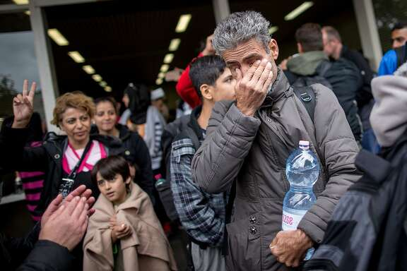 "A refugee cries as he arrives at the main station in Dortmund, western Germany, on September 6, 2015. Thousands more migrants streamed into Germany on September 6, 2015, greeted with cheers and ""welcome"" signs, as Pope Francis called on every Catholic parish in Europe to take in a refugee family. AFP PHOTO / DPA / MAJA HITIJ   GERMANY OUTMAJA HITIJ/AFP/Getty Images"