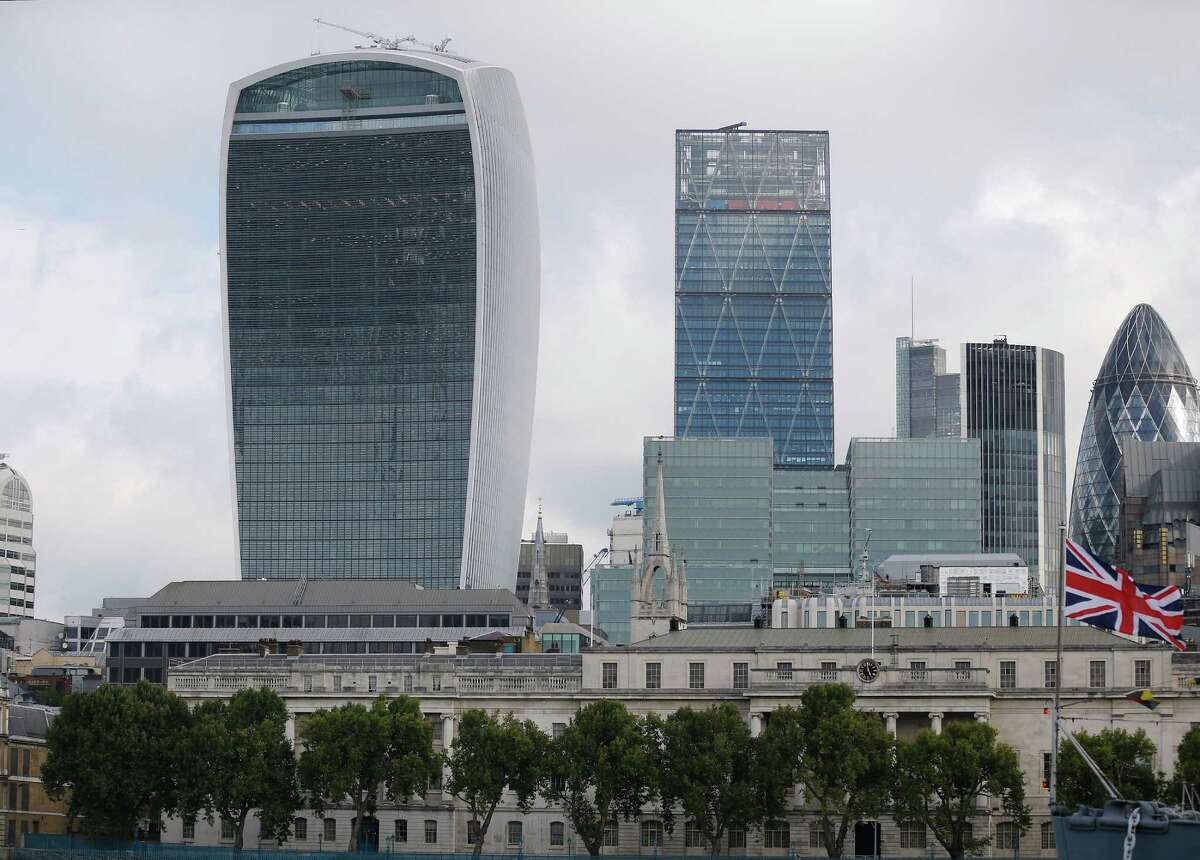 London's Walkie Talkie building, left, was judged UK's worst building in London, Wednesday, Sept. 2, 2015. A City of London skyscraper, nicknamed the Walkie Talkie, has won the annual Carbuncle Cup, awarded to a building judged to be the UK's worst. In its short history, the 37-storey office tower has melted parked cars and critics have compared its three-storey roof garden to an airport terminal.