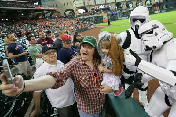 Taylor and Aria Fullbright, center left and center, take a selfie with two storm troopers before an MLB game at Minute Maid Park, Sunday, Sept. 6, 2015, in Houston.