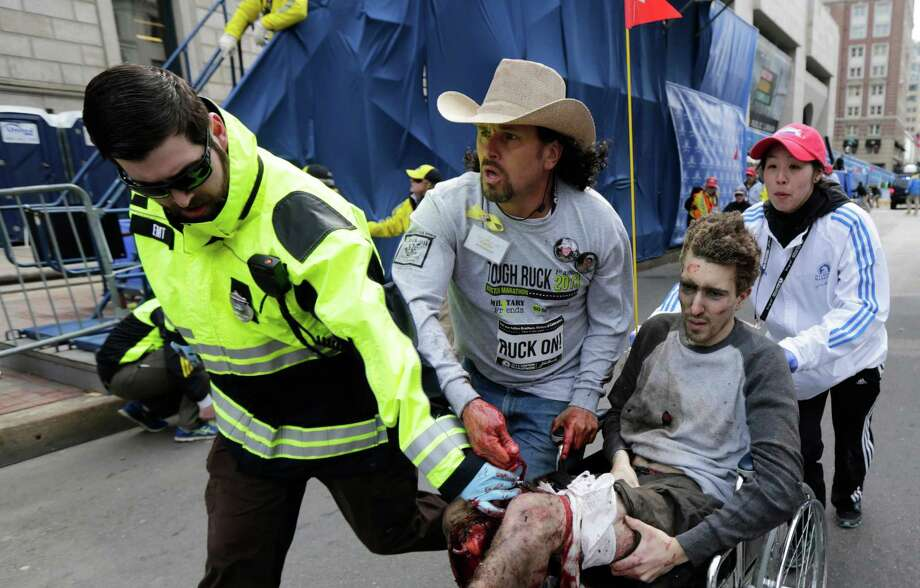 In this photo from April 15, 2013, Emergency Medical Services EMT Paul Mitchell, left, Carlos Arredondo, center, and Devin Wang, rear, push Jeff Bauman in a wheelchair after he was injured in one of two blast near the finish line of the Boston Marathon in Boston. The twin bombs near the finish line of the race killed three and injured 260 people. Bauman lost both of his legs. Photo: Charles Krupa, STF / AP