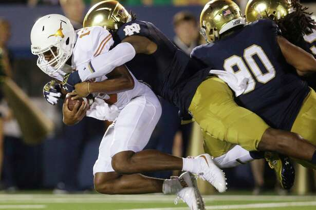 Notre Dame linebacker Jaylon Smith, center, sacks Texas quarterback Jerrod Heard, left, during the first half of an NCAA college football game Saturday, Sept. 5, 2015, in South Bend, Ind.