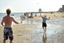 Chris Fleming, left, and son Collin, 11, of Fairfield, enjoy a game of beach paddle ball during a Labor Day weekend stay at the family beach house in Milford, Conn. on Sunday, September 6, 2015. Fleming said they had been keeping a lookout for the humpback whale that was videotaped recently off nearby Charles Island, but had made no sightings so far.