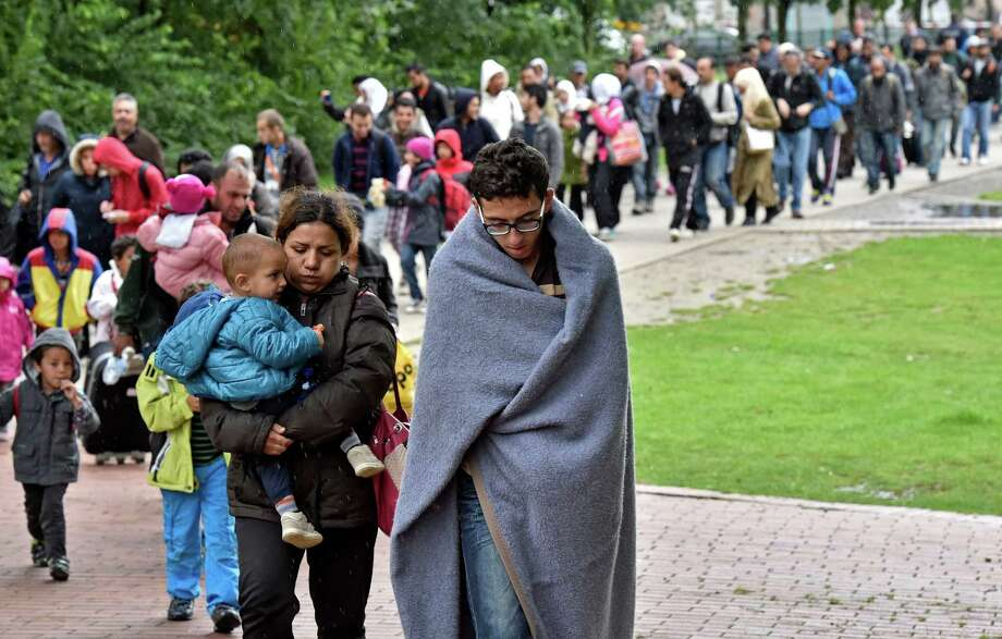 Migrants walk from the train station in Dortmund, Germany, to a processing center Sunday. Thousands arrived in Germany as Pope Francis called on Catholics to take in the refugees. Photo: Martin Meissner, STR / AP
