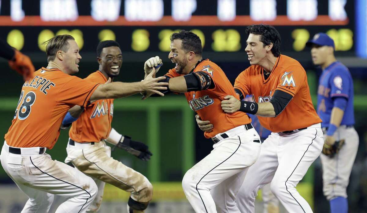 Miami Marlins' Martin Prado, second from right, is congratulated by teammates after hitting a baseball game-winning sacrifice fly with the bases loaded against the New York Mets in the ninth inning Sunday, Sept. 6, 2015, in Miami. Marlins' J.T. Realmuto scored the game-winning run in the 4-3 victory. (AP Photo/Alan Diaz) ORG XMIT: FLAD110
