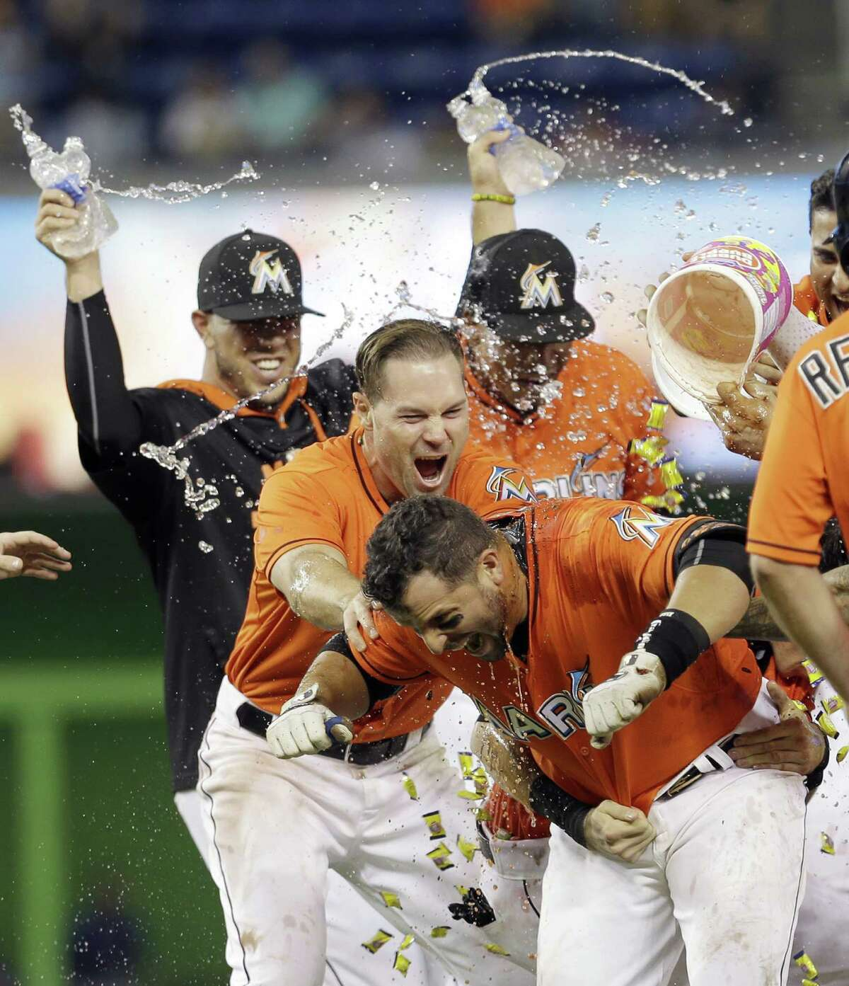 Miami Marlins' Martin Prado, foreground, is doused by teammates after hitting a baseball game-winning sacrifice fly with the bases loaded against the New York Mets in the ninth inning Sunday, Sept. 6, 2015, in Miami. Marlins' J.T. Realmuto scored the game-winning run in the 4-3 victory. (AP Photo/Alan Diaz) ORG XMIT: FLAD112