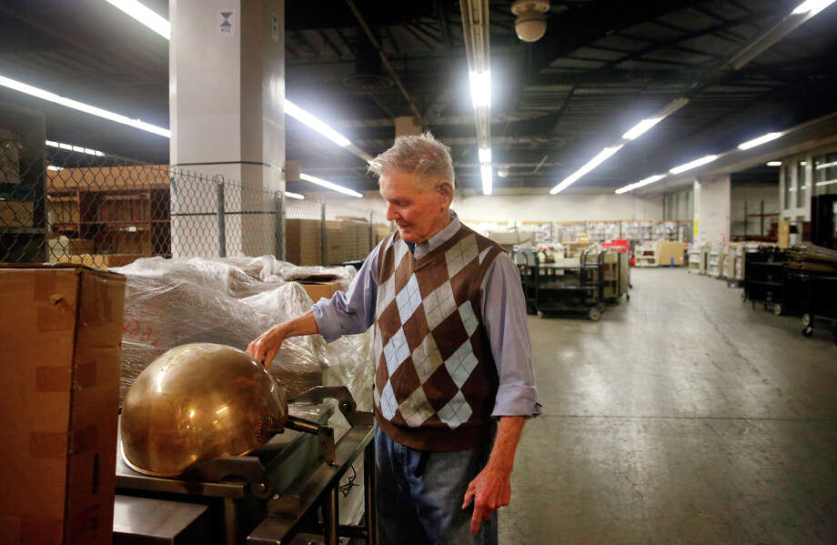 In a storage area in Brooks Hall, consultant Ken Maley looks at a cover used for serving food. Maley authored a report on how San Francisco is managing its historic artifacts. Photo: Lea Suzuki / Lea Suzuki / The Chronicle / ONLINE_YES