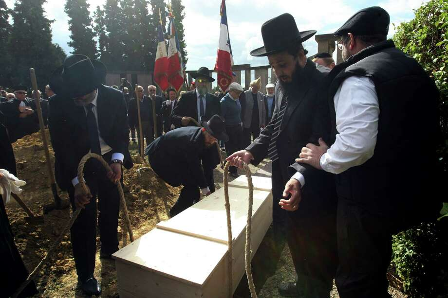 Members of the Jewish community of Strasbourg, France, lower a coffin holding the remains of several Holocaust victims of Nazi anatomist August Hirt. Photo: Christian Lutz /Associated Press / AP