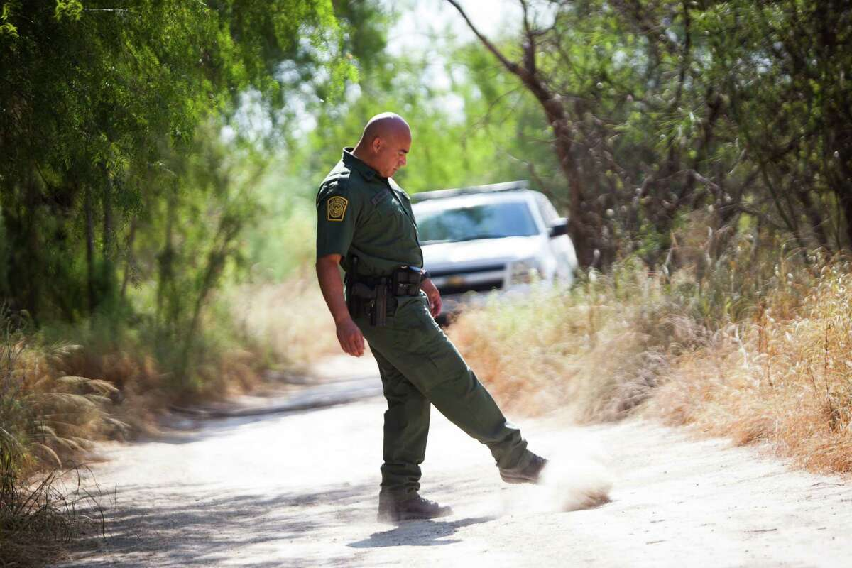 Border Patrol Agent Jose Luis Perales covers footprints on the ground in Cuevitas. Tracking footprints is one common way for agents to know how much immigrant traffic has been in certain areas.