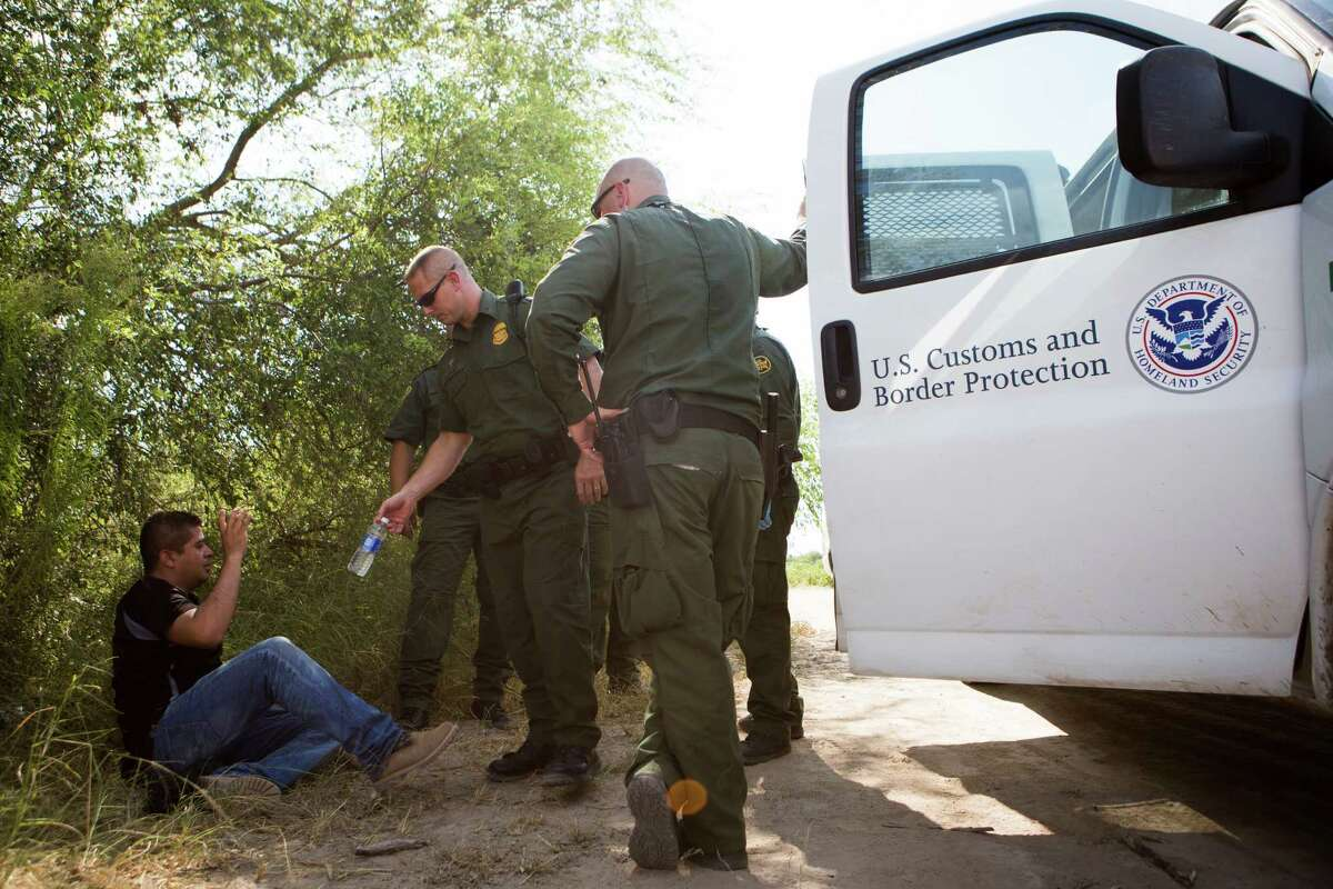 Jason Owens, center, Border Patrol agent in charge of the Rio Grande City station, gives water to a man who crossed into the United States illegally but who gave himself up in Cuevitas in desperation for water.