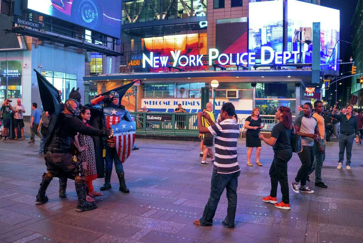 Near an New York Police Department substation, costumed character interact with visitors in Times Square Wednesday, Sept. 2, 2015, in New York. Concerned that Times Square is becoming less wholesome, the NYPD is assigning plainclothes officers to discourage aggressive panhandling in a tourist attraction that long ago rid itself of prostitutes and junkies. (AP Photo/Craig Ruttle) ORG XMIT: NYCR202