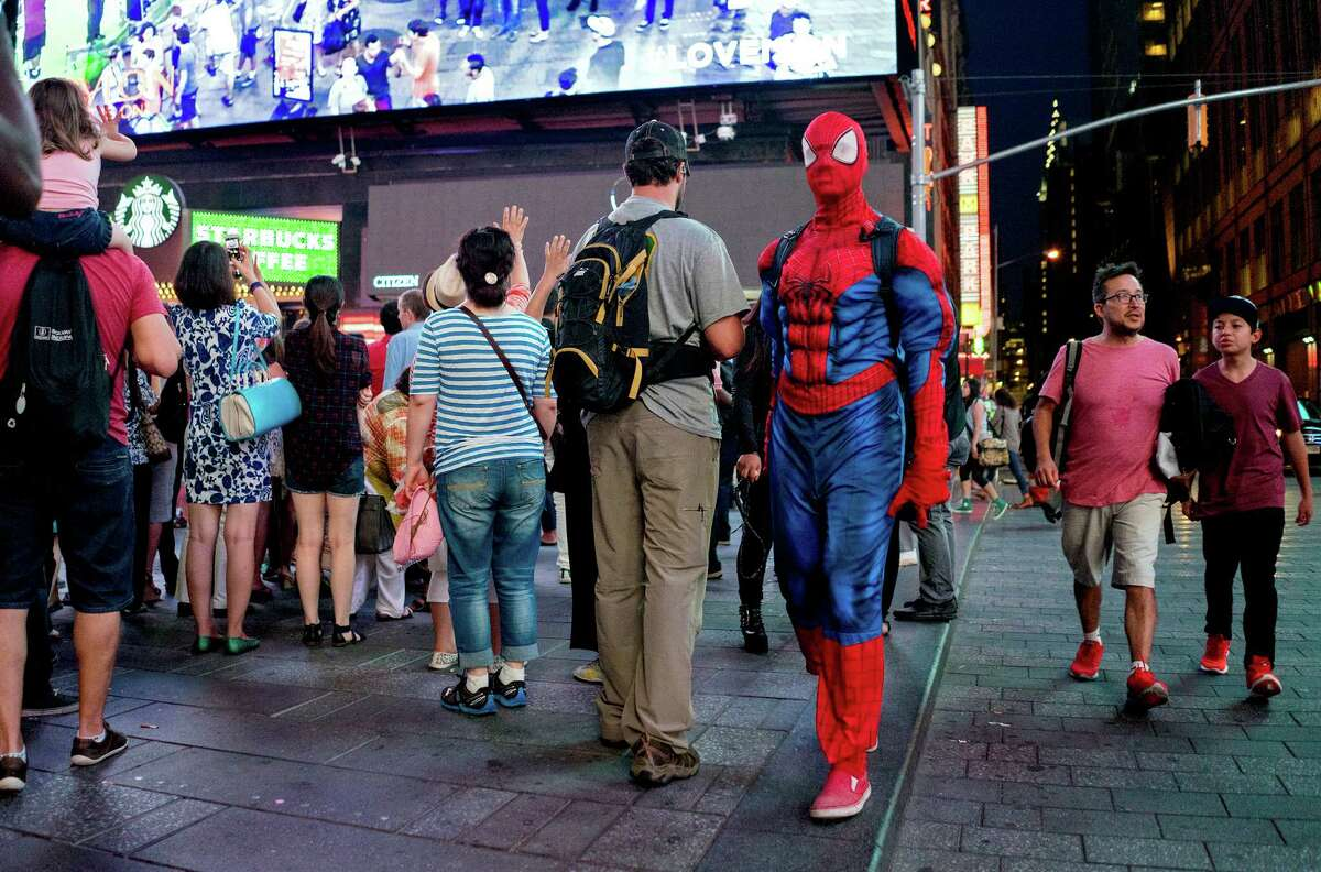 A costumed character walks past a New York Police Department officer in plain clothes Wednesday, Sept. 2, 2015, in New York's Times Square. Concerned that Times Square is becoming less wholesome, the NYPD is assigning plainclothes officers to discourage aggressive panhandling in a tourist attraction that long ago rid itself of prostitutes and junkies. (AP Photo/Craig Ruttle) ORG XMIT: NYCR203