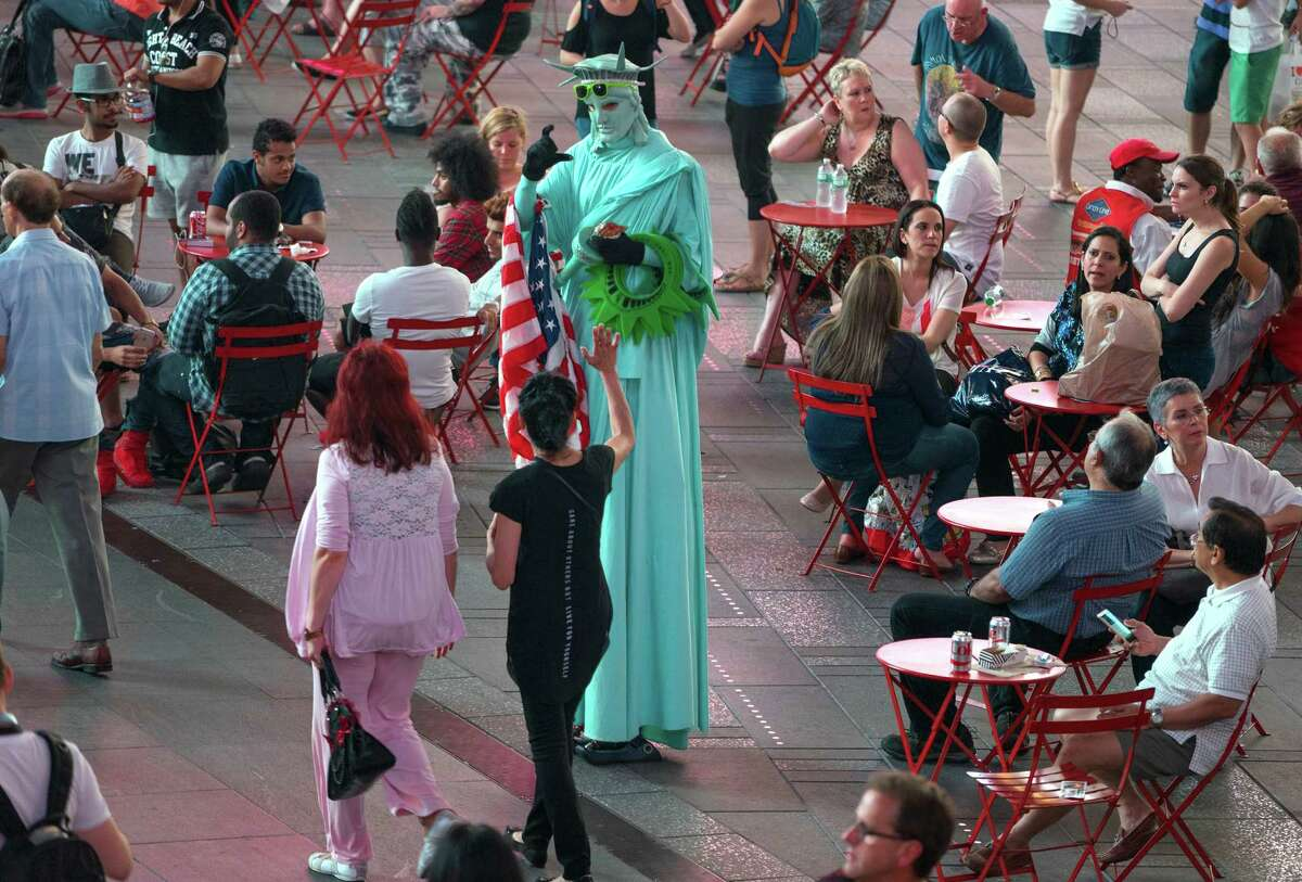 A costumed character dressed as the Statue of Liberty interacts with visitors in Times Square Wednesday, Sept. 2, 2015, in New York. Concerned that Times Square is becoming less wholesome, the NYPD is assigning plainclothes officers to discourage aggressive panhandling in a tourist attraction that long ago rid itself of prostitutes and junkies. (AP Photo/Craig Ruttle) ORG XMIT: NYCR201