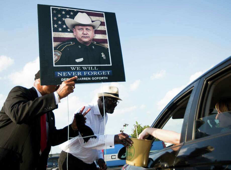 Carl Johnson holds a sign with the photograph of slain deputy Darren Goforth as he and Maurice Lam Jr. collect money from drivers at Southmore Boulevard and Texas 288 to give to Goforth's family.  Photo: Marie D. De Jesus, Staff / © 2015 Houston Chronicle