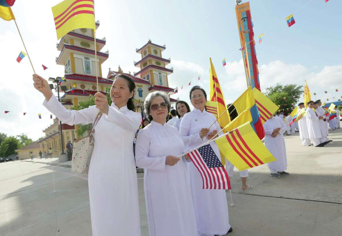From left, Anh Ngoc Truong, Huong Nguyen and Tuyet Le greet those gathered to celebrate the church opening Sunday.