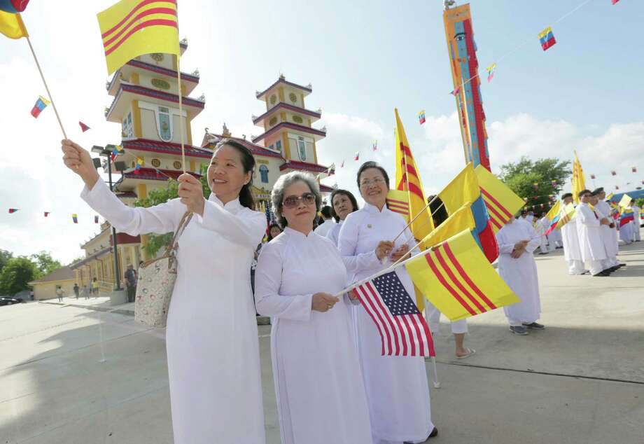 From left, Anh Ngoc Truong, Huong Nguyen and Tuyet Le greet those gathered to celebrate the church opening Sunday. Photo: Jon Shapley, Staff / © 2015 Houston Chronicle