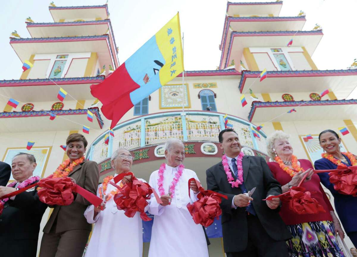 From left, Kelly Sargeant, Kham Pham, The Quoc Trinh, a Reverend of Cao Dai High Temple, Mayor Pro-Tem Ed Gonzalez and Olga Bennett take part in the ribbon-cutting ceremony during the festivities for opening of the Cao Dai Temple on Sunday in southwest Houston.