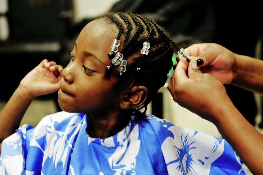 Averi Julien, 4, of Schenectady gets the finishing touches on her new braids at Jade's Hair Envy during the Eighth Annual Community Cuts & Styles event on Sunday, Sept. 6, 2015, in Colonie, N.Y.  The event is put on by The Capital District Chapter of the National Pan-Hellenic Council, Inc. in conjunction with BrickOs Barber Shop, Jay Allen Barber Studio, JadeOs Hair Envy, New York State United Teachers, Capital District Chamber of Commerce and WAMC.  Nine different barbershops and hair salons in Albany, Colonie and Schenectady took part in this years program which gives free haircuts and styles for students from pre-kindergarten through 12th grade.  Children were also given new backpacks filled with school supplies.  (Paul Buckowski / Times Union) Photo: PAUL BUCKOWSKI / 00033228A