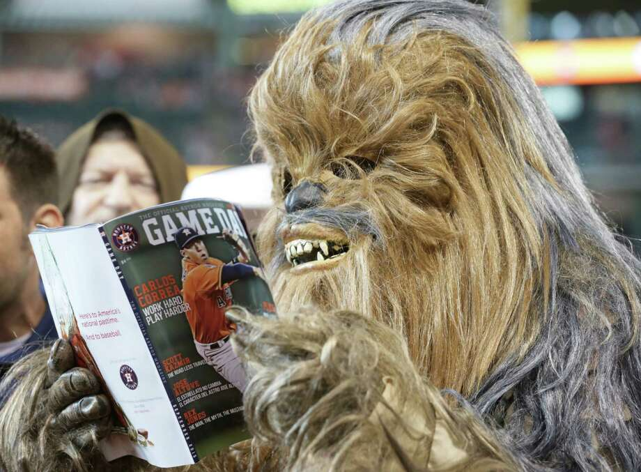 """Chewbacca"" reads a copy of the Astros' Game Day magazine before the team played the Twins on Sunday afternoon. The costume reflected the Astros' commemoration of ""Star Wars Day."" Photo: Jon Shapley, Staff / © 2015 Houston Chronicle"