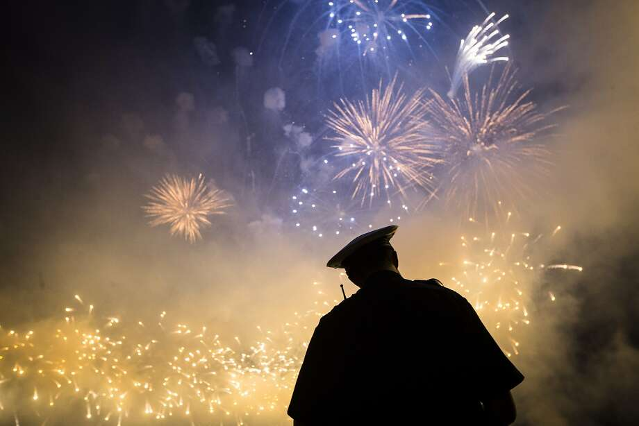 A Cincinnati Police officer stands beneath a Labor Day fireworks display as part of the city's Riverfest celebration on the Ohio River, Sunday, Sept. 6, 2015, in Cincinnati. The annual end-of-summer festival culminates with Rozzi's Famous Fireworks display, which draws thousands to the banks of the river in downtown Cincinnati and northern Kentucky. Photo: John Minchillo, Associated Press