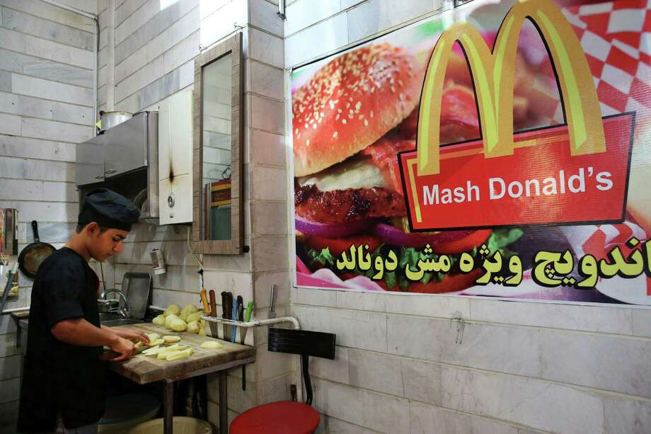 "In this Wednesday, Aug. 5, 2015 photo, Iranian worker Shahin Mirouzadeh cuts potatoes at ""Mash Donald's"" fast food restaurant, a knock-off version of McDonald's in western Tehran, Iran. Businesses worldwide want to get into Iran, home to some 80 million people, oil and gas reserves and a middle class eager for familiarity with brands based in the U.S. Though hard-liners worry that could corrupt the Islamic nation, others have opened their mind to the idea of having them around. (AP Photo/Vahid Salemi) Photo: Vahid Salemi / Associated Press / AP"