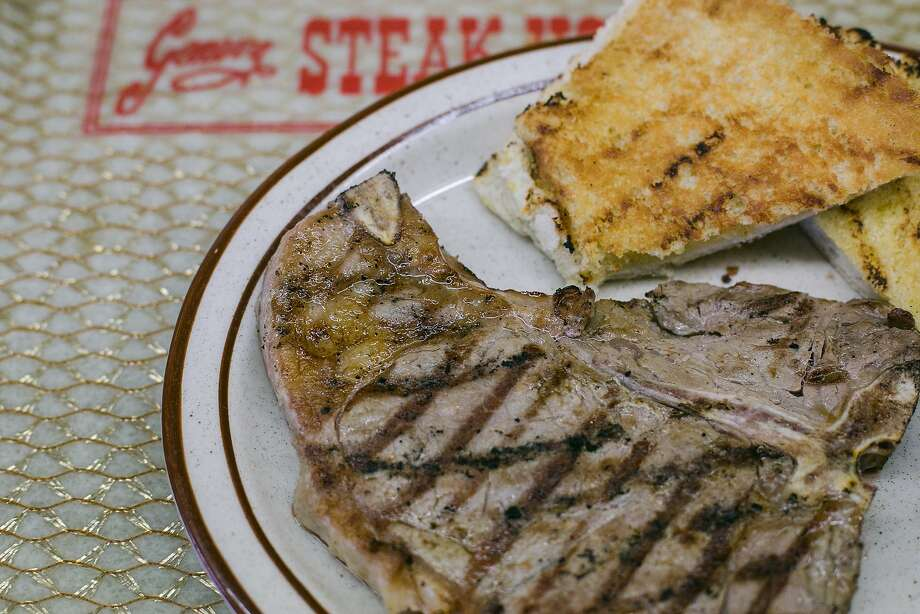 A T-bone steak with garlic bread served on their signature gold trays at Geneva Steak House. Photo: Jen Fedrizzi, Special To The Chronicle