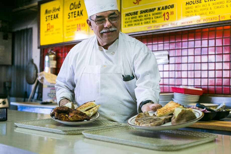Juan Cruz sets down a steak dinner and a freshly cooked chicken at Geneva Steak House. Photo: Jen Fedrizzi, Special To The Chronicle